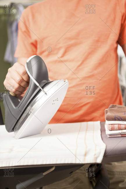 Close up of person wearing bright orange top ironing kitchen towels on ironing board and using modern iron appliance