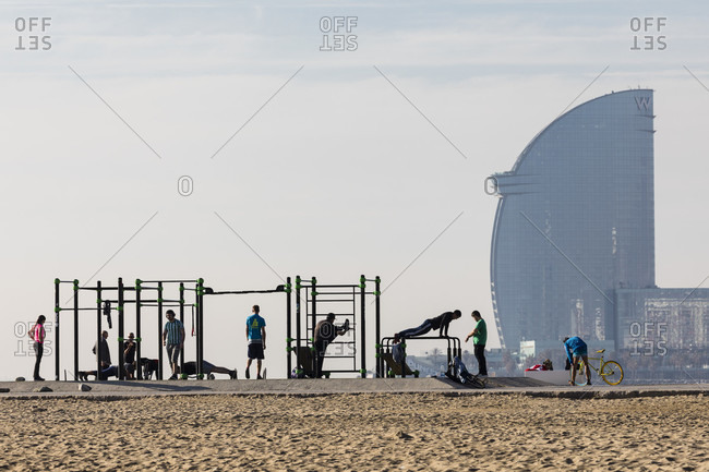 February 22, 2017: Outdoor training spot (street workout) by the beach in front of hotel w Barcelona in the distance, port Olympic, Barcelona, Catalonia, Spain