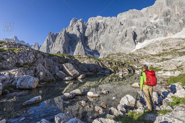 Backpacker near the glacial lake of popera, vallon popera, comelico superiore, auronzo comelico and sexten dolomites, belluno, veneto, italy
