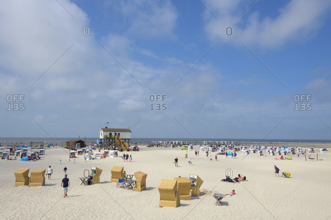 August 6, 2019: Beach chair and bathing tourists in summer, norderdeich, sankt peter-ording, north friesland, north sea, schleswig-holstein, Germany