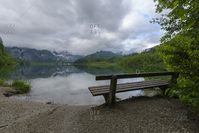 Mountain lake with bench after rain in summer, almsee, almtal, upper austria, austria