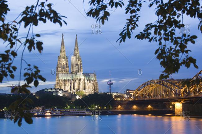 Illuminated cologne church and hohenzollern bridge and river rhine, dusk
