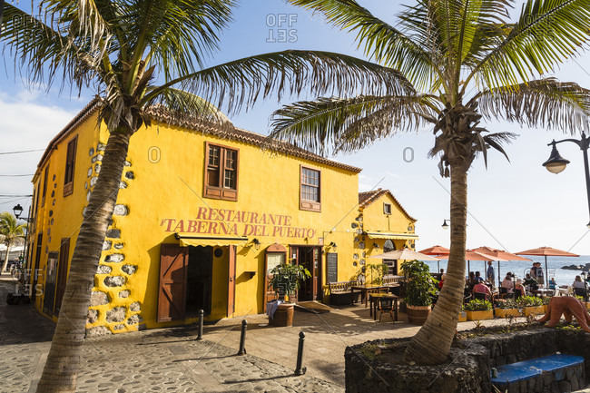 March 16, 2014: Colorful restaurant 'taberna del puerto' framed by palm trees