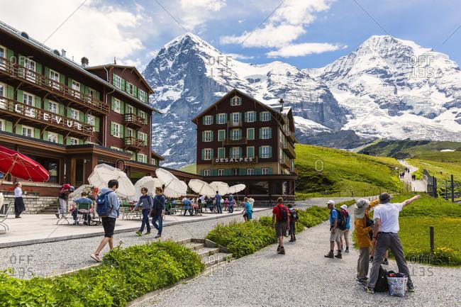 July 16, 2014: Tourists by hotel bellevue and desalpes near the railway station cog railway jungfraubahn in front of mount eiger (3.970 m) and mount moench (4.107 m), kleine scheidegg