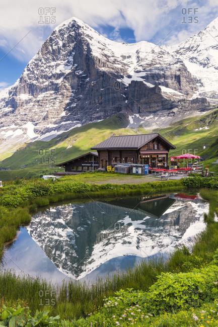 July 16, 2014: Chalet and mount eiger (3.970 m) reflecting in a pond, kleine scheidegg