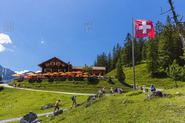 July 17, 2014: Swiss national flagg by mountain inn at lake oeschinensee, unesco world heritage site, bernese oberland