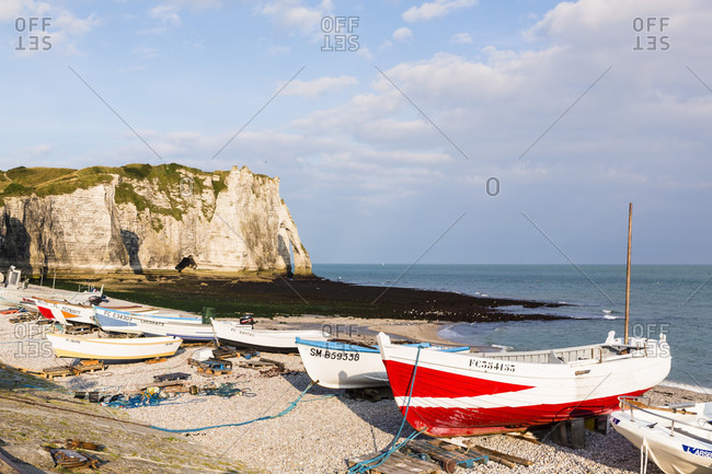 July 30, 2014: Fishing boats on the beach in front of the rock formation port d'aval cliff, a natural arch, cote d'albatre, the alabaster coast, pays de caux, seine-maritime