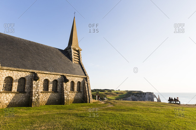 Chapel notre-dame de la garde and the rock formation port d'aval cliff, a natural arch in the distance, cote d'albatre, the alabaster coast, pays de caux, seine-maritime