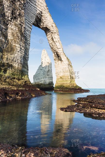 Sharp rocks in front of the rock formation port d\'aval cliff, a natural arch, cote d\'albatre, the alabaster coast, pays de caux, seine-maritime