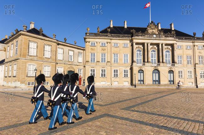 Change of guards on the cobblestone courtyard at amalienborg palace (rococo) in copenhagen, öresund, seeland