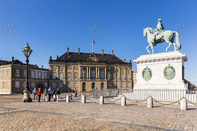 September 3, 2014: Statue of king frederick v in front of amalienborg palace (rococo) on cobblestone courtyard in copenhagen, öresund, seeland