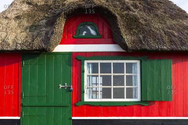 Red thatched roof beach hut, close-up of grren door and window, aero island