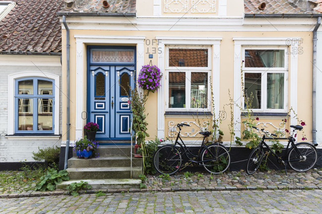 September 5, 2014: Two bicybles in front of a house with a blue door in a cobblestone alley of aeroskobing, aero island