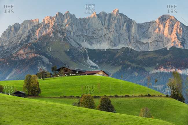 Meadow and farm in front ot the mountain range 'wilder kaiser' at sunset, autumn