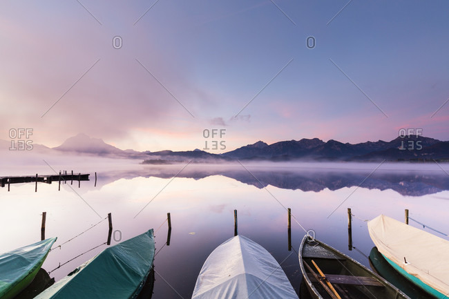 Moored rowing boats at dawn on lake hopfensee, autumn