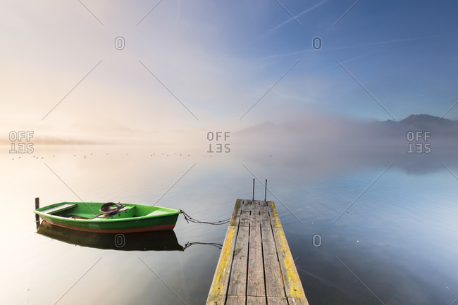 Moored rowing boat by a jetty in morning fog, morning mood at lake hopfensee, autumn