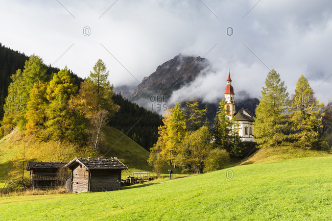 St.-nikolaus church surrounded by autumnal larch trees, cloud covered tribulaun mountain range, autumn, obernbergtal, wipptal, brenner region
