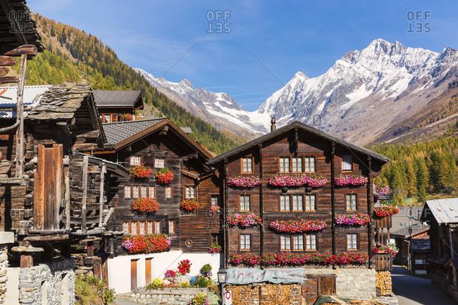 Traditional valais houses in front of sattelhorn (3.741 m) and schinhorn (3.797 m), loetschental, jungfrau region, unesco world heritage region, autumn