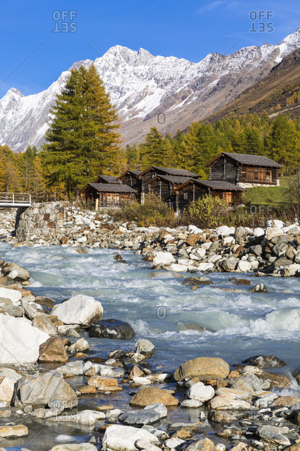 Huts by the river lonza in front of schinhorn (3.797 m), loetschental, jungfrau region, unesco world heritage region, autumn