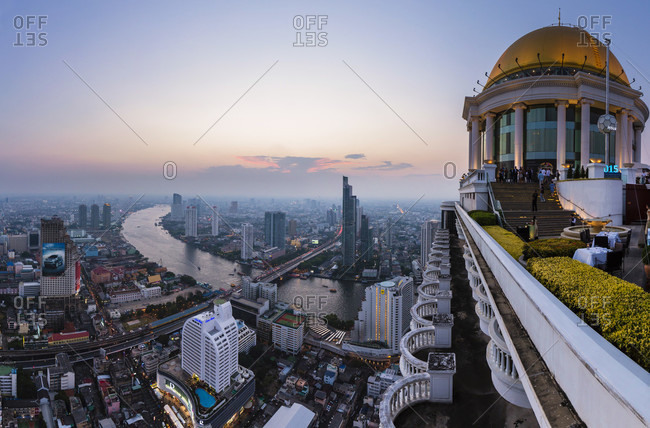 February 16, 2015: Elevated view on bangkok and chao praya river, the dome and sky bar on 64th floor of the state tower, highest open roof bar of its kind in the world, dusk