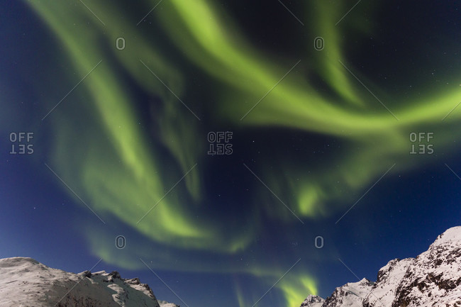 Northern lights or aurora borealis in the fjord landscape of tromsoe, ersfjord