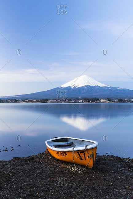 April 15, 2015: Orange rowing boat on the shore at lake kawaguchi in front of mount fuji, dawn