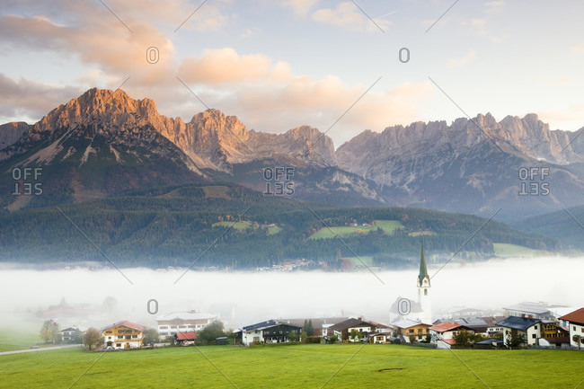 Village of ellmau below wilder kaiser mountains in morning fog, sunrise