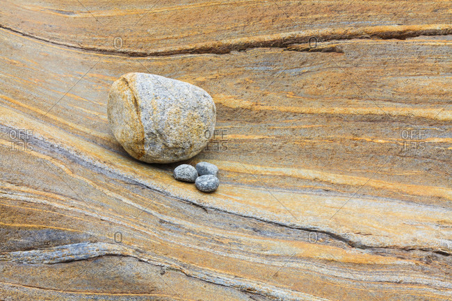 Round shaped stone and little pebbles on a rock surface showing lines in different colors