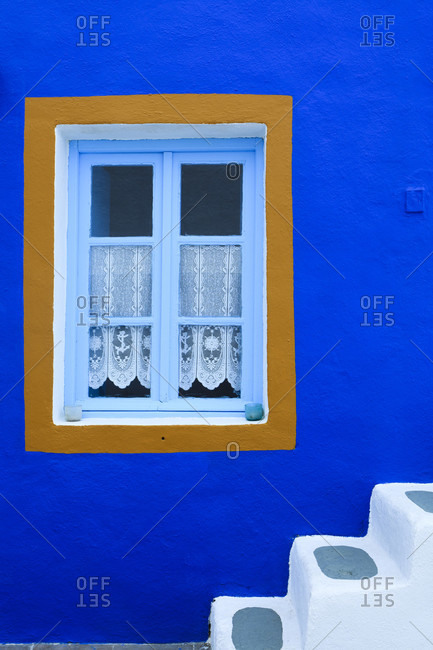 Blue painted house and white stairway, detail of window and stairs