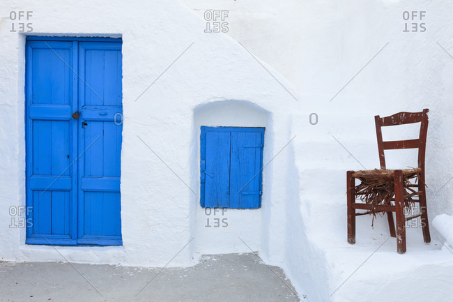 Blue painted closed door and window shutter by an old chair by white washed stairs