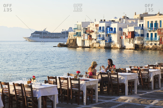 May 8, 2017: Two young women sitting at a restaurant table at little venice by the aegian sea at sunset, cruise ship azamara quest moored in the background