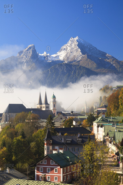 Low clouds at berchtesgaden town skyline with church and watzmann moutain in the background, autumn,