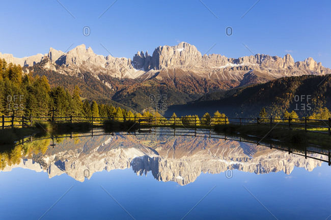 Rosengarten mountain range and a rising moon reflecting in a lake, autumn, unesco world heritage site