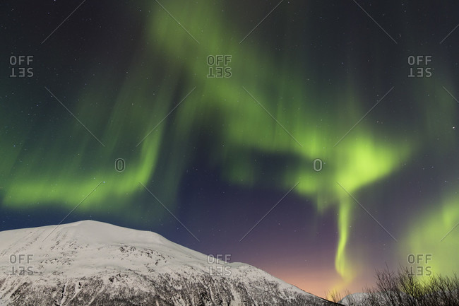 Northern lights (aurora borealis) above snow covered mountains at a fjord in the norway arctic