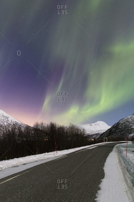 Northern lights (aurora borealis) above a road and snow covered mountains in the norway arctic