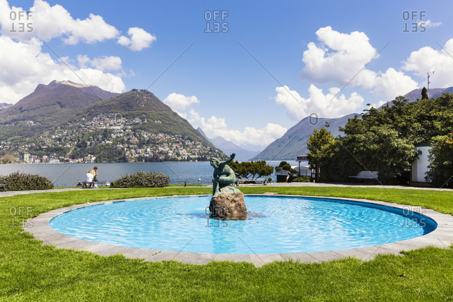 June 2, 2018: Sculpture in a fountain by a promenade in front of monte bre at lago lugano, spring