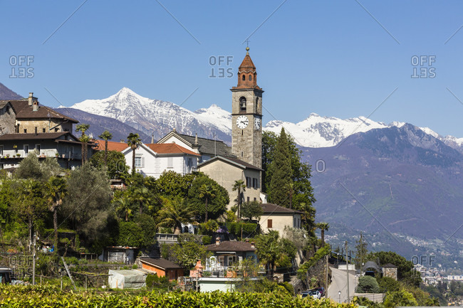 Parish church san martino in front of snow covered mountians and lago maggiore below, spring