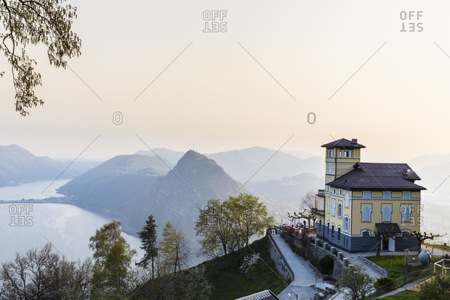 Elevated panorama view from restaurant 'vetta' on lake lugano and monte san salvatore at sunset, spring