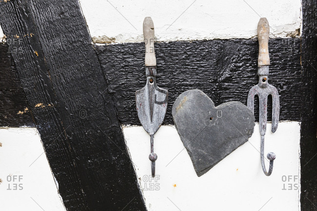 Garden utensils as a cloth hook and a heart made of slate rock on a half-timbered house wall in a garden, close-up