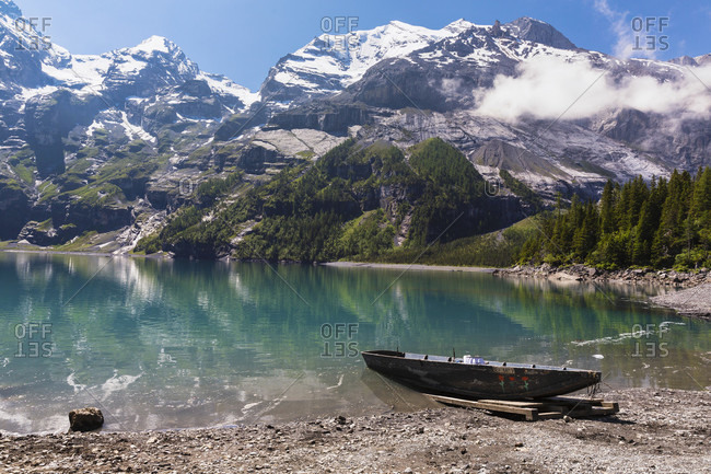 June 2, 2018: Old rowing boat at the shore of lake oeschinensee within the steep mountains of the doldenstock range above kandersteg with its canadian wilderness charme, jungfrau-aletsch unesco world heritage site