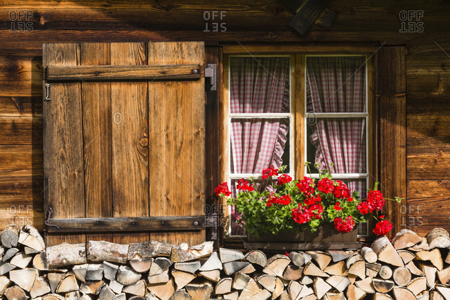 Window with geranium flower box and stapled fire wood at a wodden chalet