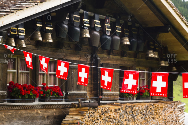 Swiss flaggs for decoration in front of a log home with huge cow bells hanging from a wall