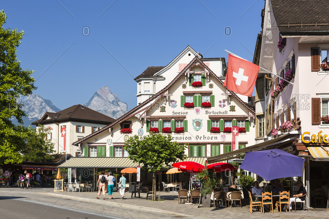 June 2, 2018: People sitting beneath sun umbrellas in front of a typical house fassade