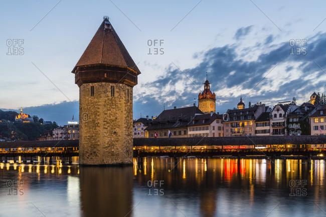 June 2, 2018: Illuminated chapel bridge (kapellbruecke) and water tower over the reuss river with the town hall behind, dusk