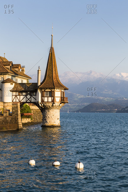 Oberhofen castle at lake thun, eiger, moench and jungfrau mountains in the distance, sunset