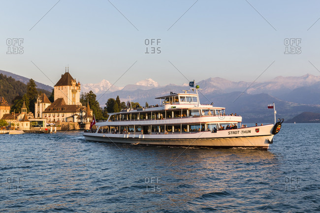 June 2, 2018: Leaving side-wheeler at oberhofen castle at lake thun with eiger, moench and jungfrau mountains in the distance, sunset