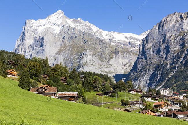 Chalets in front of mount wetterhorn, bernese alps, unesco world heritage site