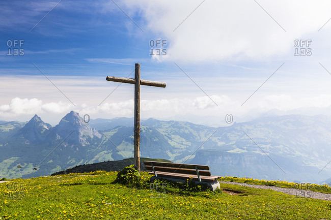 Wodden cross beside a bench on mount fronalpstock 1,922 m in front of grosser mythen 1,898 m (right) and kleiner mythen 1,438 m
