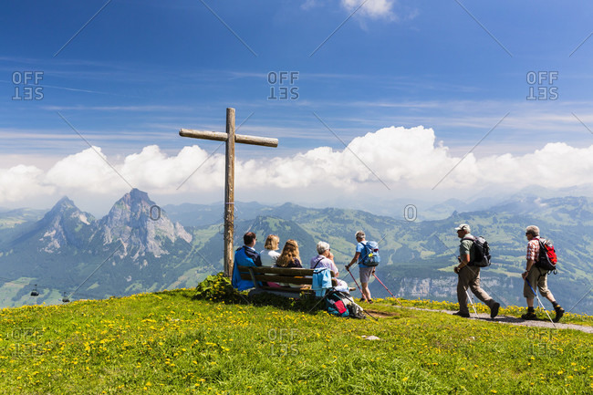May 30, 2018: Wodden cross beside a bench on mount fronalpstock 1,922 m in front of grosser mythen 1,898 m (right) and kleiner mythen 1,438 m