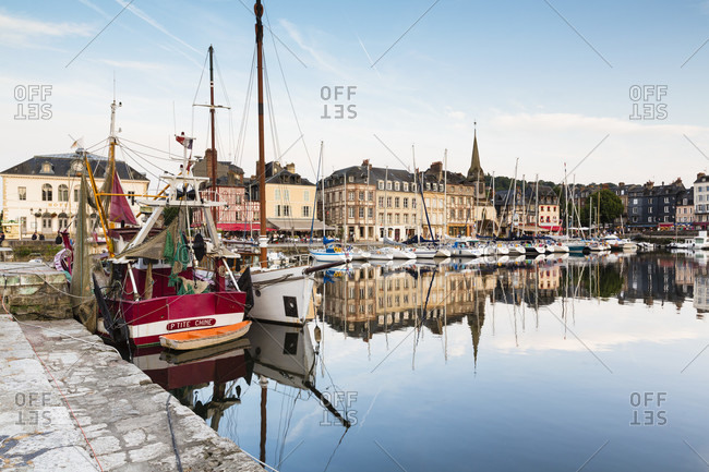 May 30, 2018: Sailing boats in front of houses at the waterfront reflecting in the beautiful picturesque port of honfleur, calvados, seine-maritime, basse-normandy